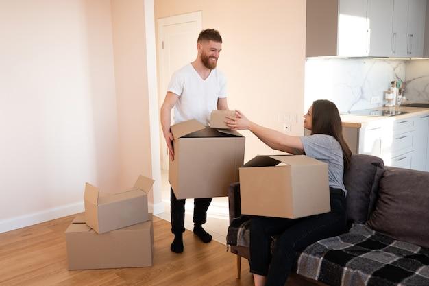 Meisje geeft kartonnen doos met dingen aan haar vriendje thuis. glimlachend europees paar vrouw en man. concept van verhuizen in nieuwe flat. idee van jong gezin. interieur van studio-appartement. zonnige dag