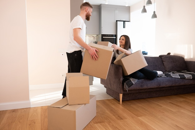 Meisje geeft kartonnen doos met dingen aan haar vriendje thuis. vrolijke europese paar vrouw en man. concept van verhuizen in nieuwe flat. idee van jong gezin. interieur van studio-appartement. zonnige dag