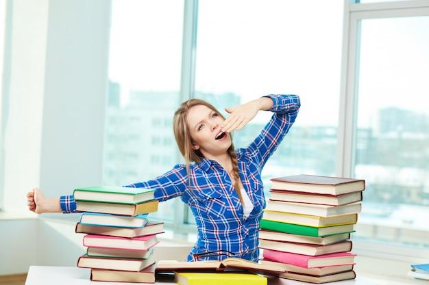 Meisje geeuwen omringd door boeken