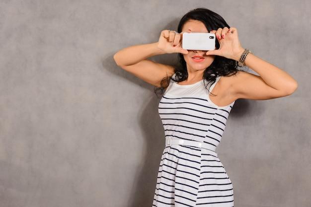 Meisje gefotografeerd op een mobiele telefoon op een grijs