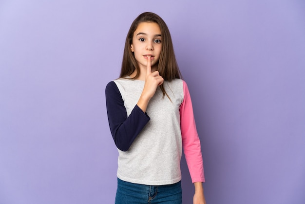 Meisje geïsoleerd met een teken van stilte gebaar vinger in de mond steken