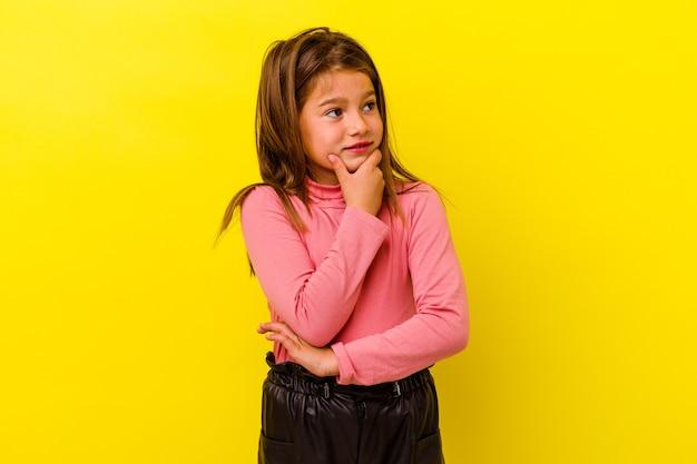 Meisje geïsoleerd op gele muur denken en kijken, reflecterend zijn, nadenken, een fantasie hebben