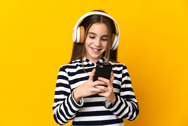 Meisje geïsoleerd op gele muur muziek luisteren en kijken naar mobiel