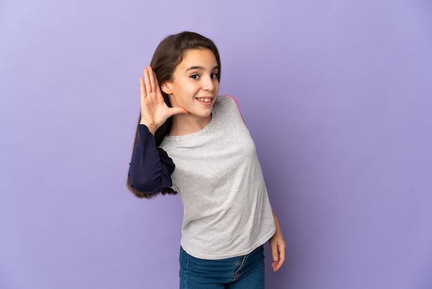 Meisje geïsoleerd op paarse achtergrond luisteren naar iets door hand op het oor te leggen