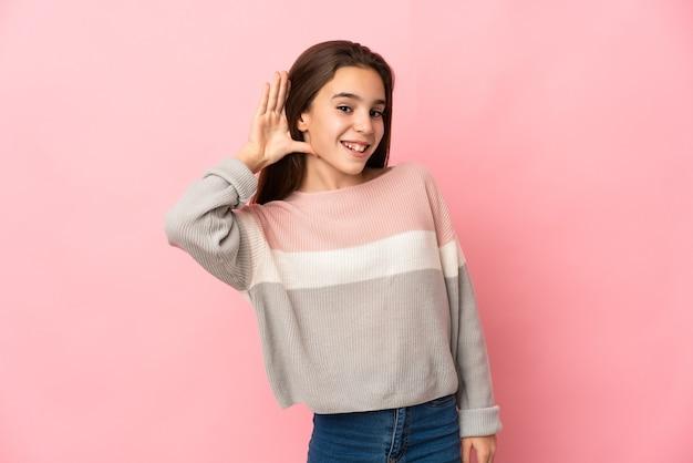 Meisje geïsoleerd op roze achtergrond luisteren naar iets door hand op het oor te leggen