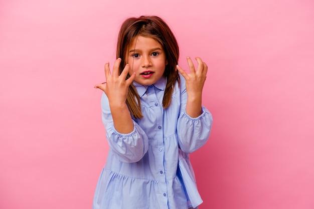 Meisje geïsoleerd op roze muur boos schreeuwen met gespannen handen