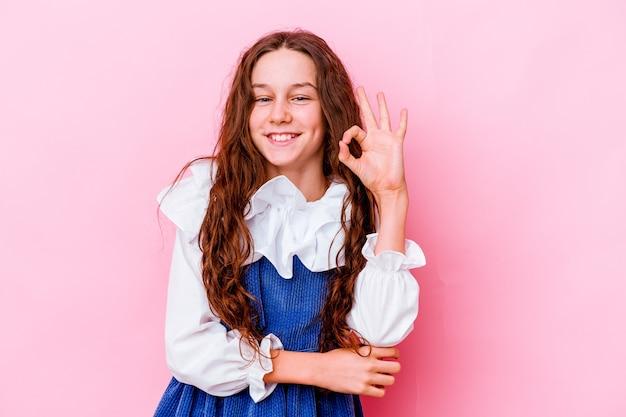 Meisje geïsoleerd op roze muur knipoogt en houdt een goed gebaar met de hand