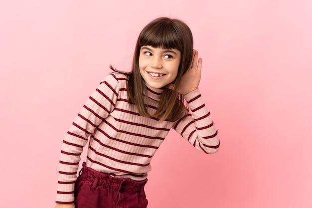 Meisje geïsoleerd op roze muur luisteren naar iets door hand op het oor te leggen