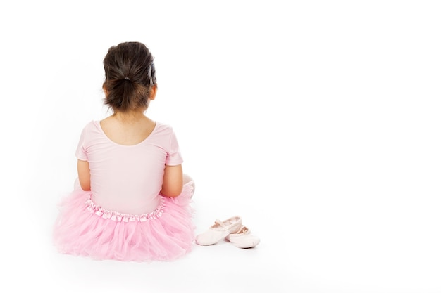 Meisje gekleed als balletdanser zit op de vloer