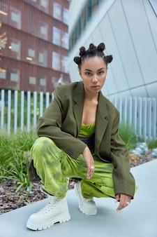 Meisje gekleed in groene formele jas losse broek en witte laarzen poseert tegen stedelijke gebouwen buitenshuis