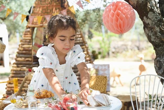 Meisje gekleed in het wit dekt de tafel om te vieren met haar vrienden