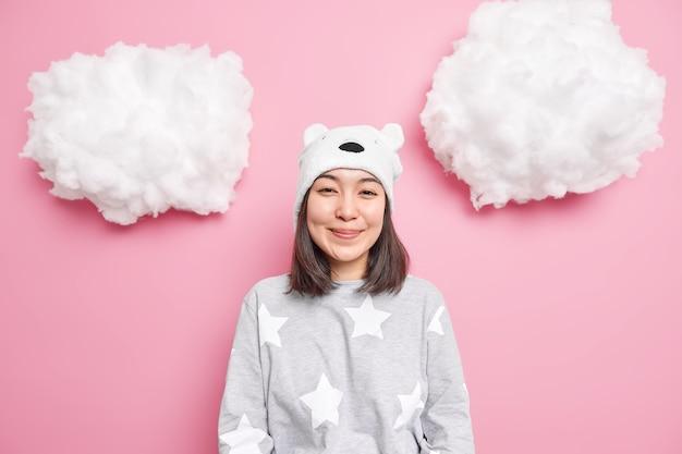 Meisje gekleed in huishoudelijke kleding hoort positief nieuws geïsoleerd op roze