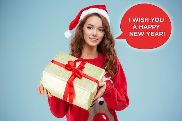 Meisje gekleed in kerstmuts met een kerstcadeau. ze kijkt naar de camera. vakantieconcept met blauwe achtergrond.