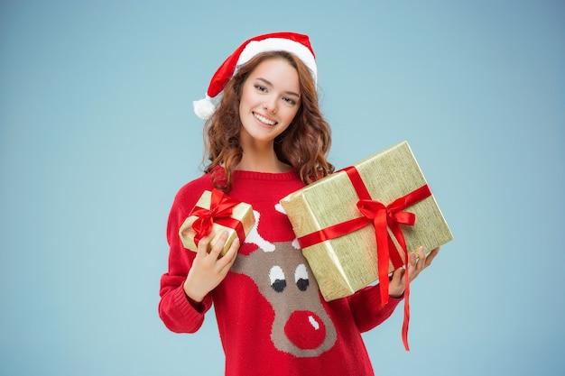 Meisje gekleed in kerstmuts met een kerstcadeau
