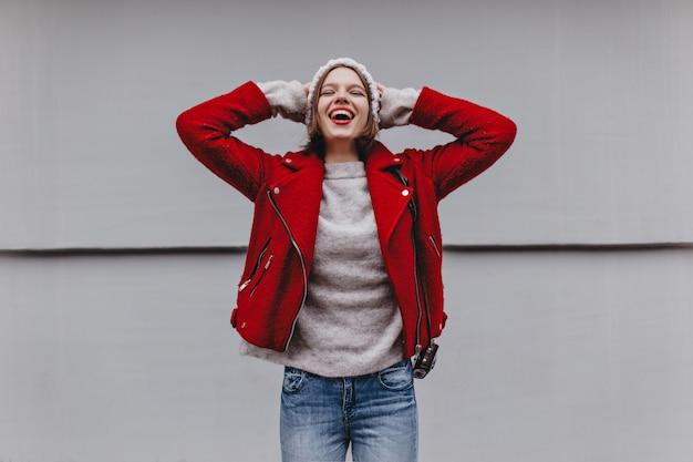 Meisje gekleed in rood jasje, lichte spijkerbroek en kasjmier trui zet haar hoed op en lacht tegen een witte muur.
