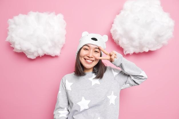 Meisje gekleed in slaappak toont vredesgebaar dichtbij het leven geniet van het leven glimlacht zorgeloos poseert vrolijk kantelt hoofd geïsoleerd op roze