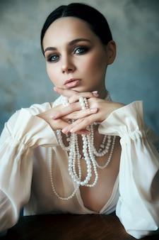 Meisje gekleed in witte boho kleding met witte parel kralen om haar nek zit aan een tafel.