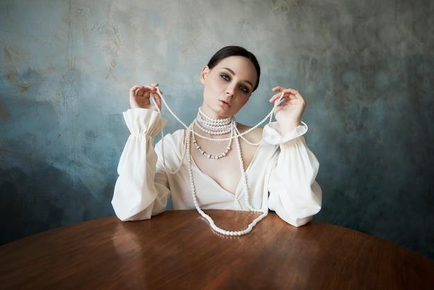 Meisje gekleed in witte boho kleding met witte parel kralen om haar nek zit aan een tafel