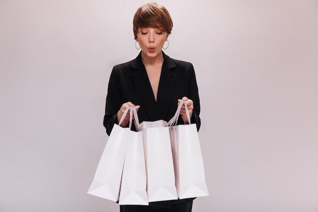 Meisje gekleed in zwarte jas kijkt naar boodschappentassen met interesse. verrast jonge vrouw in pak vormt met pakketten op geïsoleerde achtergrond