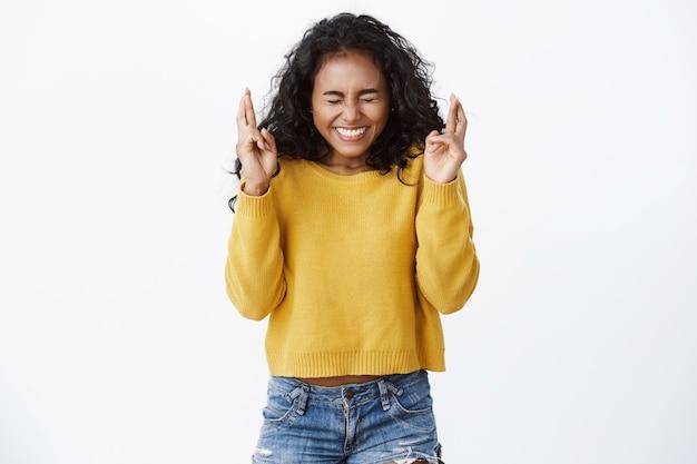 Meisje gelooft dat dromen uitkomen, sluit ogen gelukkig lachend, kruis vingers veel geluk, anticiperend op positief nieuws, staande witte muur optimistisch