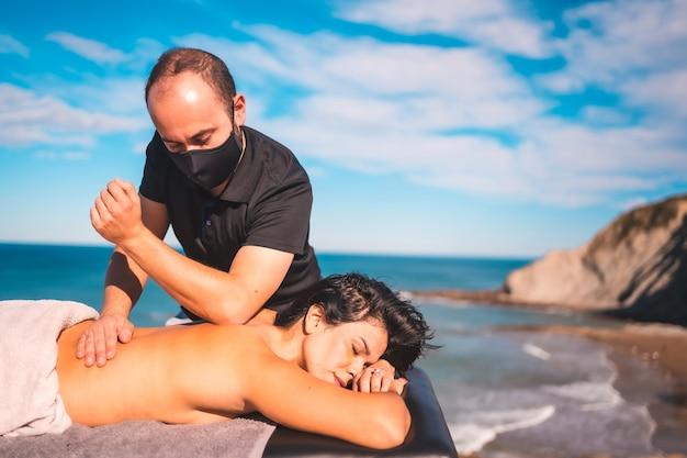 Meisje geniet van de massage aan de kust bij de zee, masseuse met gezichtsmasker in de coronavirus-pandemie