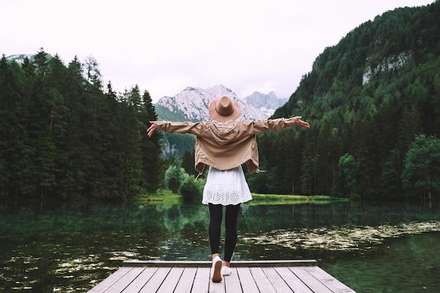 Meisje geniet van de schoonheid van de natuur en kijkt naar het bergmeer avontuurlijke reizen in slovenië europa