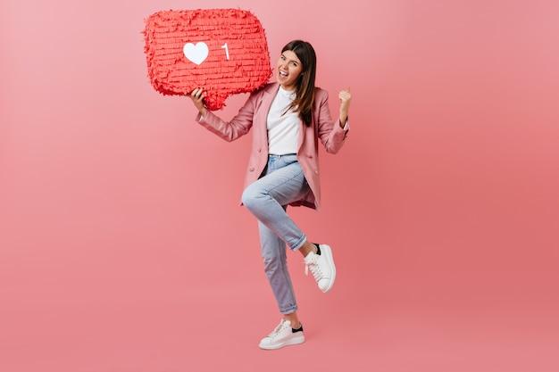 Meisje geniet van feedback op sociaal netwerk. studio shot van jonge vrouw dansen met like icoon op roze achtergrond.