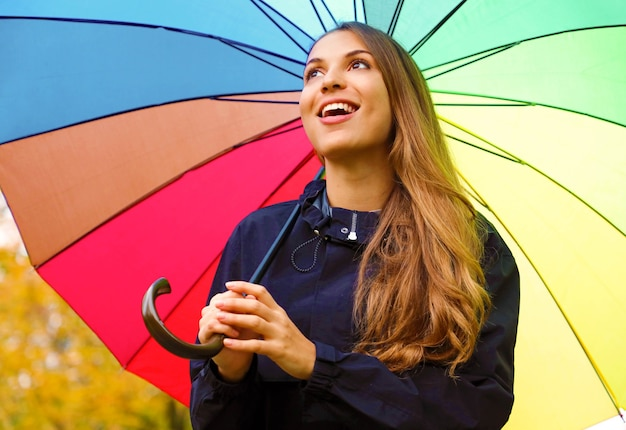 Meisje genieten van regenachtige herfstdag kijken naar hemel vrolijk glimlachen