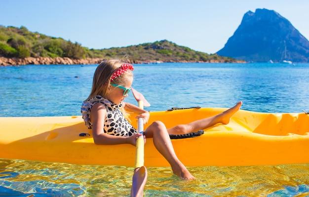 Meisje genieten van zwemmen in gele kajak in het heldere turquoise water
