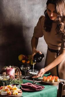 Meisje giet champagne in een glazen tafel met vruchtenkaastaart, foto van hoge kwaliteit