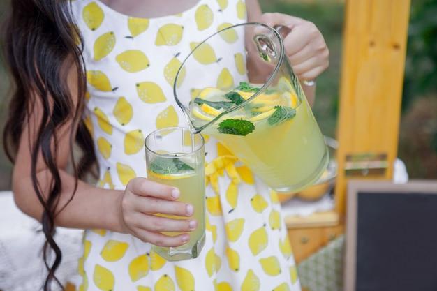 Meisje giet limonade met munt uit een karaf in een glas