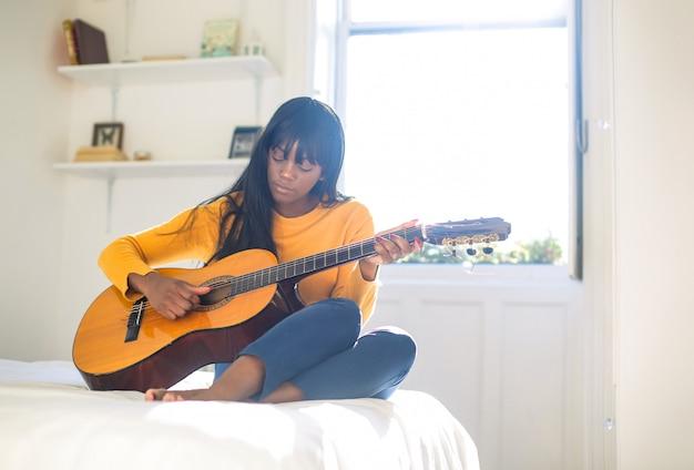 Meisje gitaarspelen in haar slaapkamer