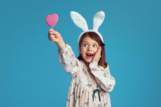 Meisje glimlacht en houdt het smakelijke koekje van de zoete hartvorm die konijntjesoren draagt