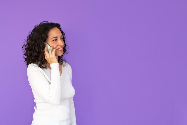 Meisje glimlacht tijdens het praten aan de telefoon. paarse achtergrond en kopie ruimte. wit casual overhemd. gekruld haar.