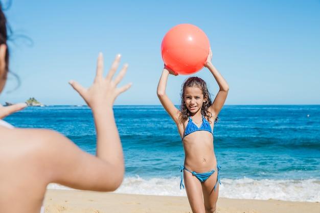 Meisje gooien de bal naar haar zus