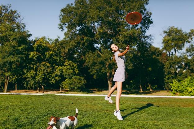 Meisje gooit oranje vliegende schijf naar kleine grappige hond, die hem op groen gras vangt. kleine jack russel terrier huisdier buiten spelen in het park. hond en eigenaar op open lucht. dier in beweging achtergrond.
