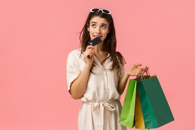 Meisje gretig verspillen meer geld schuldig bijten creditcard en kijken nadenkend aarzelend omhoog, denken, proberen te stoppen met het kopen van nieuwe dingen, shoppaholic bedrijf boodschappentassen, roze achtergrond