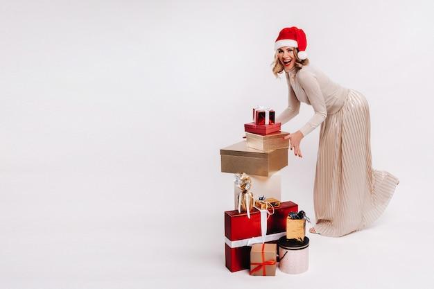 Meisje grijpt kerstcadeaus staande op de vloer op een wit.