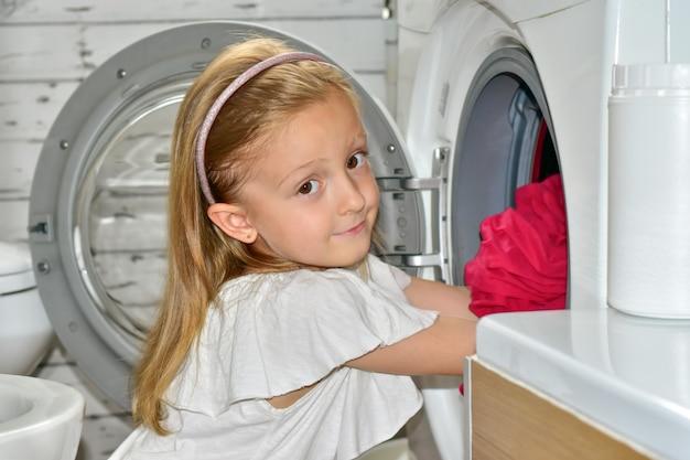 Meisje haalt oranje en roze lakens uit een wasmachine