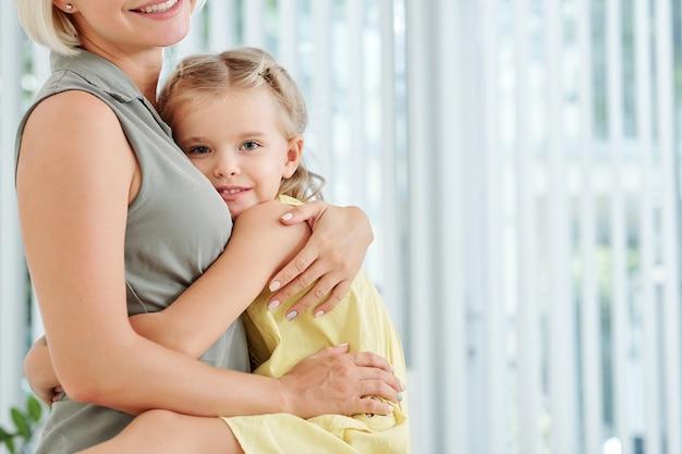Meisje haar moeder stevig knuffelen