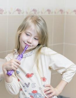 Meisje haar tanden poetsen in de badkamer met terneergeslagen ogen.