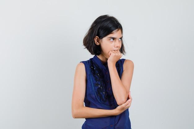 Meisje haar vuist in blauwe blouse bijten en vergeetachtig op zoek. vooraanzicht.
