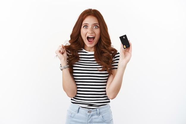 Meisje had geluk ontving extra cashback voor online internetaankoop, kijk enthousiast schreeuw gefascineerd lachend geamuseerd, toont zwarte creditcard, kreeg een uitstekend aanbod van de bank, open aanbetaling