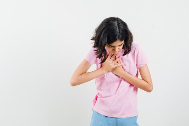 Meisje hand in hand op de borst in roze t-shirt en op zoek dankbaar. vooraanzicht.