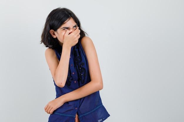 Meisje hand in hand op mond terwijl lachen in blauwe blouse vooraanzicht.