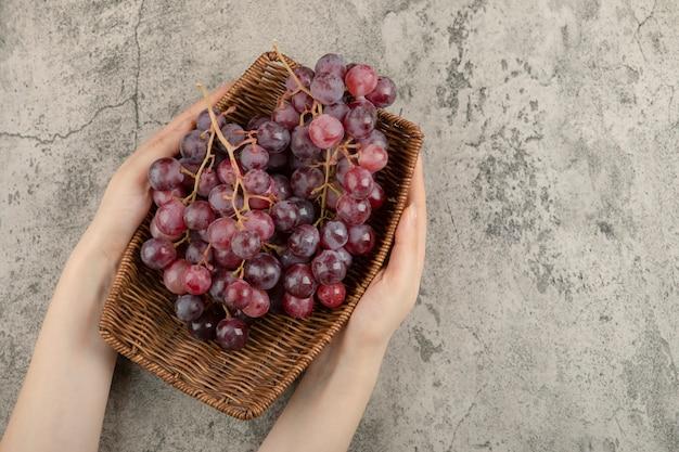 Meisje hand met mand van rode druiven op marmer.