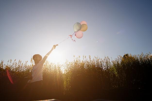 Meisje hand met multicolor ballonnen gedaan op de gele bloementuin. ontspan concept. retro filter effect selectieve focus.