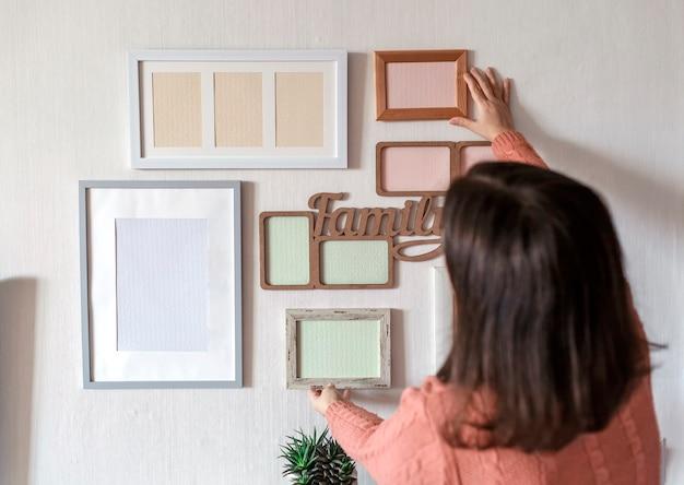 Meisje hangend frame op witte muur met set van verschillende lege verticale en horizontale fotolijsten om een familiefotogalerij te maken, om een moment vast te leggen, mockupsjabloon op witte muur, levensstijl