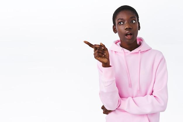 Meisje heeft een interessant idee, attente aantrekkelijke afro-amerikaanse vrouw met kort haar, hipster roze hoodie