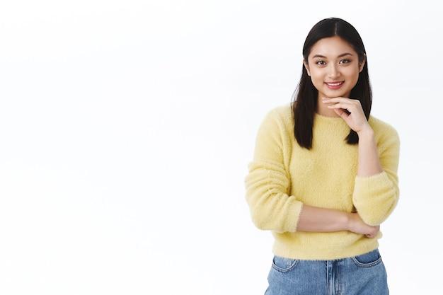 Meisje heeft een interessant idee, overweegt iets, kijkt doordachte camera. aziatische mooie vrouw die lacht, een glanzende, perfecte huid aanraakt, make-up of koreaans huidverzorgingsproduct promoot, witte muur